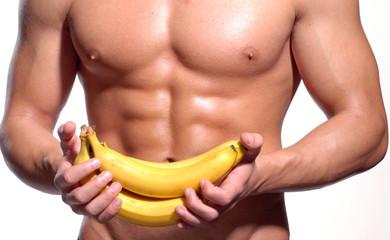 Hombre saludable y fuerte sujetando bananas,abdominales.