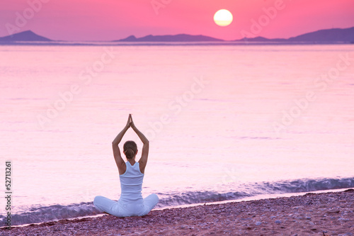 Caucasian woman practicing yoga at seashore