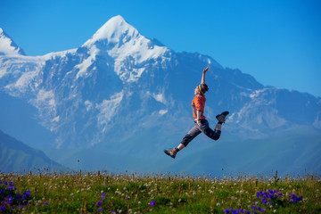 Hikier jumps on meadow against big Caucasus mountains