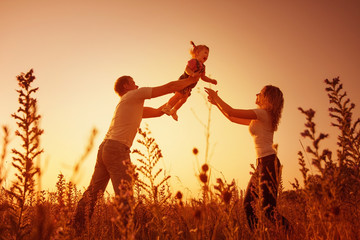 happy family outdoor, silhouettes on sunset