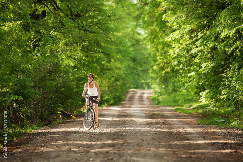 Biker on forest road at sunrise