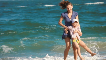 young woman with a child playing on the beach