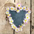 Schiefertafel in Herzform mit Gänseblümchen