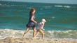 mother and son running together on the beach