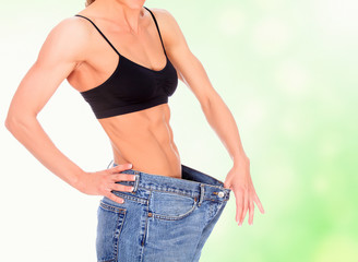 woman with strong abs shows her old big jeans