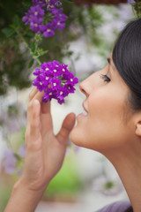 Woman smelling purple flower