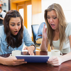 Women looking shocked at tablet pc in canteen