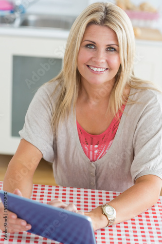 Smiling woman working on digital tablet
