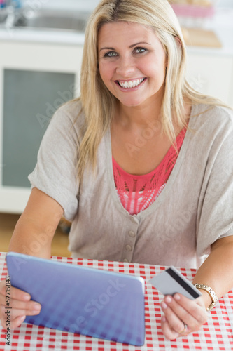 Smiling woman shopping online with her digital tablet