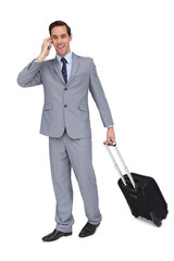 Happy young businessman with his luggage while phoning