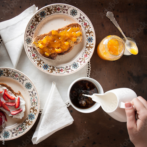 Hand pouring milk on coffee on a romantic breakfast table
