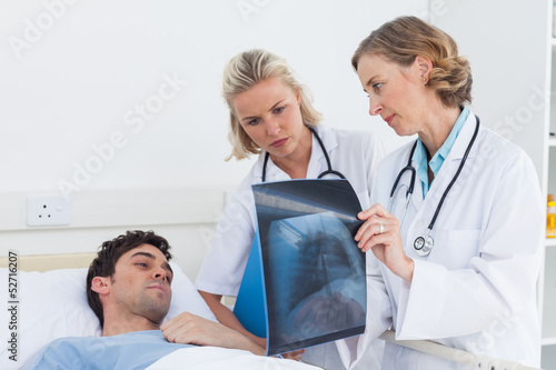 Doctors showing radiography to a patient