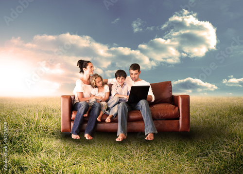 Happy family using the laptop in a field