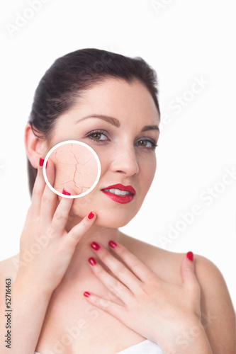 Attractive woman rubbing her skin with close up of her wrinkles