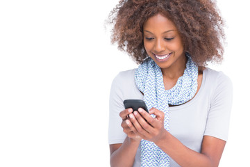 Cheerful woman typing a text message on her smartphone
