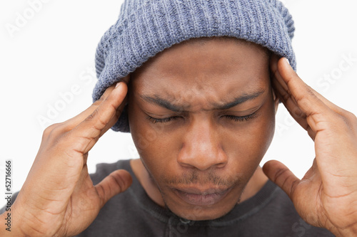Man in beanie hat grimacing with pain of headache