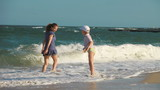 Mom and young son wet his feet in the sea, laugh and run away