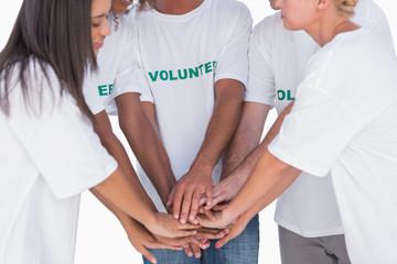 Happy volunteers putting hands together