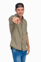 Man smiling and wearing baseball hat backwards and pointing