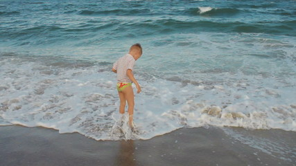 little boy playing with the waves