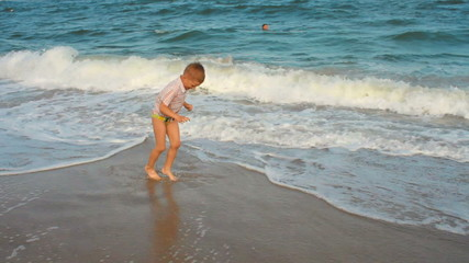 little boy jumping over the waves and running on the beach