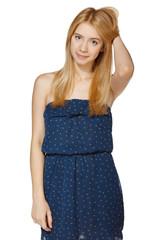 Smiling female in blue sundress posing wiht hand in hair