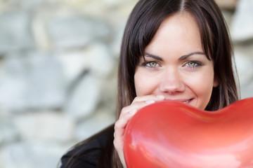 Lächelnde Frau mit Herzluftballon