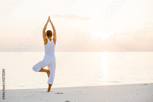 Leinwandbild Motiv Caucasian woman practicing yoga at seashore