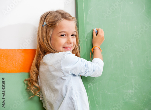 Girl Writing On Green Chalkboard In Classroom