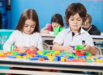 Children Playing With Construction Blocks In Classroom