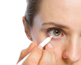 Closeup on woman using white eye liner