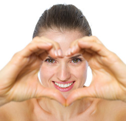 Smiling young woman looking through heart shaped hands