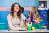 Teacher With Bored Boy Sitting At Desk In Classroom
