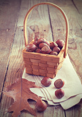 Hazelnuts (filbert) in basket on wooden background