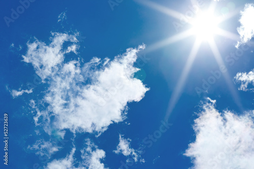 blue sky with sun and cumulus clouds