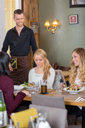 Female Friends With Food On Table While Waiter Holding Menu