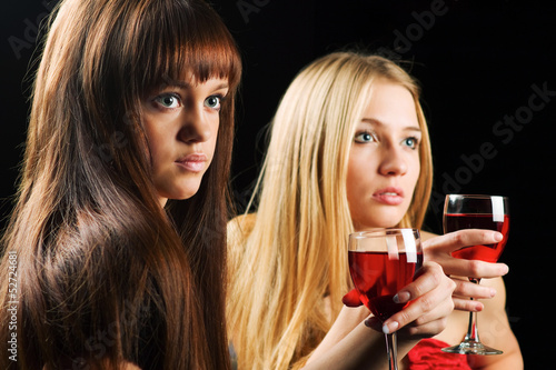 Two young women drinking red wine