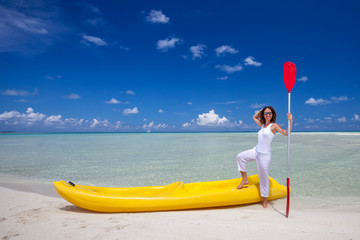 Young caucasian woman keeps paddle at the seashore near yellow k