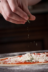 Cook putting oregano on raw pizza close-up