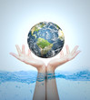 Earth in hand over water (Elements of this image furnished by NA