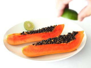 Papaya and hand squeezing lime