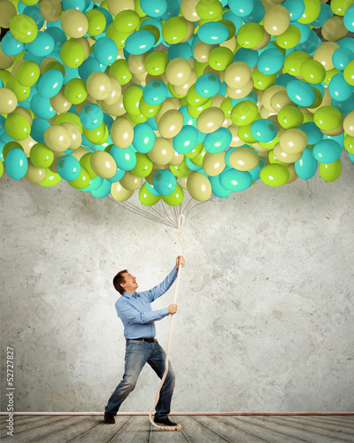 Adult man pulling a rope with balloons