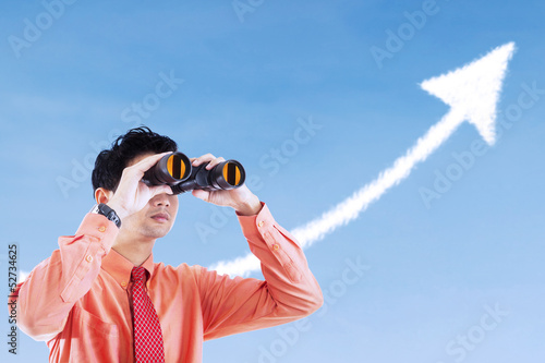 Businessman see success arrow sign using binocular