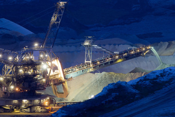 A back-filling machine in an open coal mine at night
