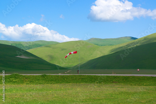 wind-sleeve on green plateau in mountains in Italy