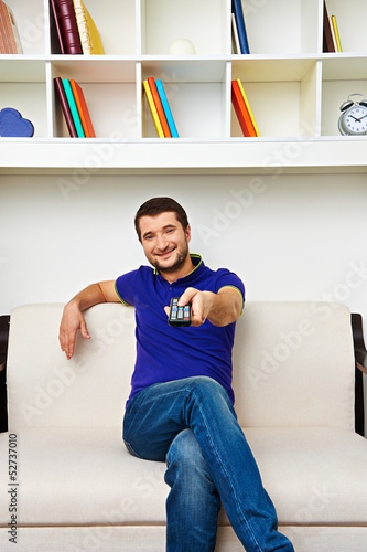 man resting on sofa and watching tv