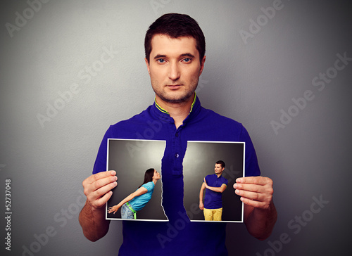 man tearing the photo of couple