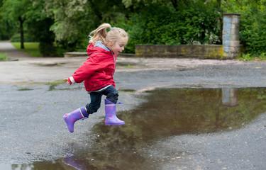 Kleines Mädchen springt über eine Pfütze