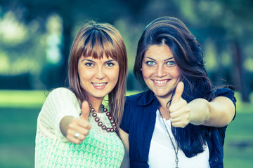 Happy Female Friends at Park with Thumbs Up