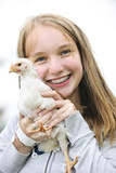 Teenage girl holding chicken